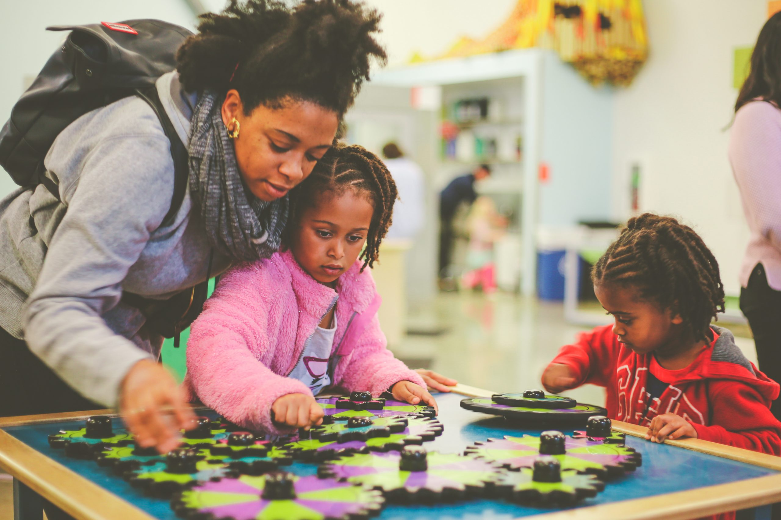 A parent and children playing at a colorful gears exhibit at a museum